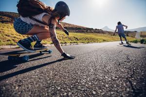 Frau mit Longboard auf der Straße