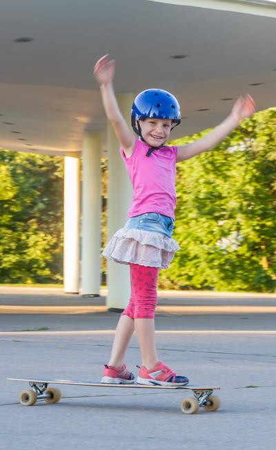 Mädchen mit Longboard und Helm