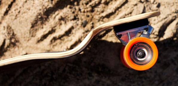 Atom Drop Down Longboard mit orangen Rollen in den Bergen