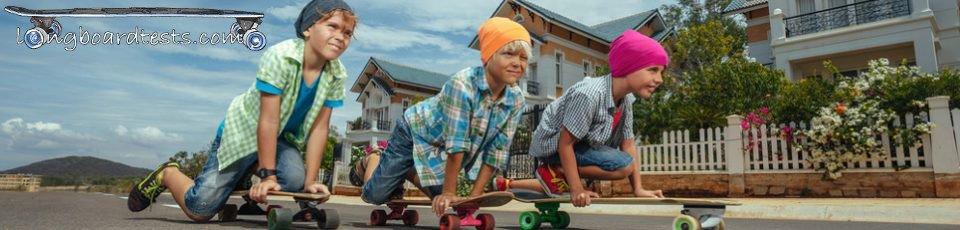 3 Kinder mit Longboard auf der Straße