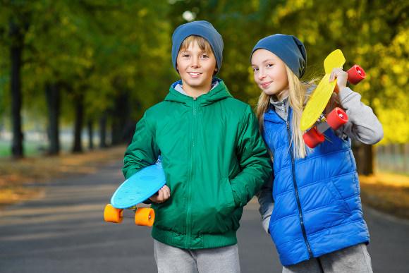 Zwei Kinder mit Mini Longboards