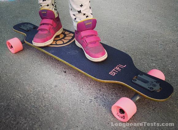 Das BTFL Polly Longboard mit pinken Rollen auf der Straße